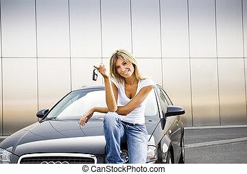 new car - Young woman holding keys to new car