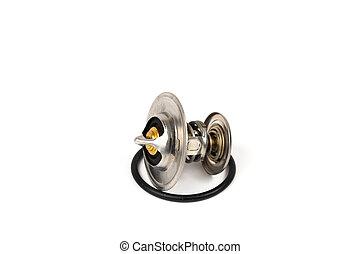 New car thermostat on a white isolated background next to a rubber gasket. Repair kit of spare parts for the replacement of the thermostat in the engine cooling system
