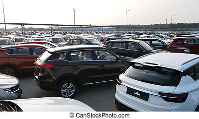 New cars lined up parking outside factory on car factory background. Industrial concept.