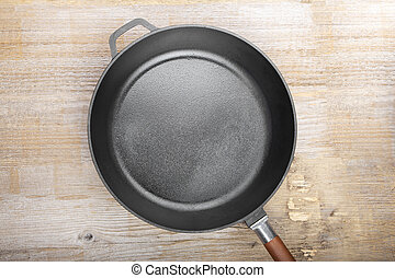 New cast-iron grill pan on a wooden background. place for ...