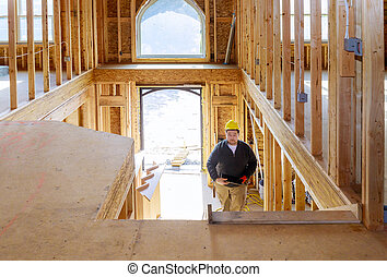 New construction house builder in hard hat walking on holding tablet PC