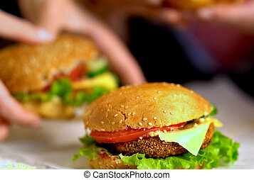 New cooking of hamburger fast food with ham on wooden board . Group of hamburger. Human hand holding cheeseburger. Sharpness in front of sandwich.