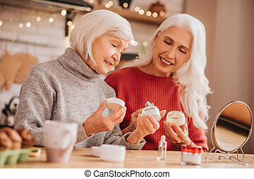 Two good-looking elderly women discussing new creams