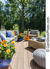 New design villa patio with rattan sofa, table, small pouf, guitar in the background
