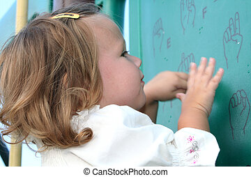 Little girl imitating sign language gestures written on a wall at a playground.
