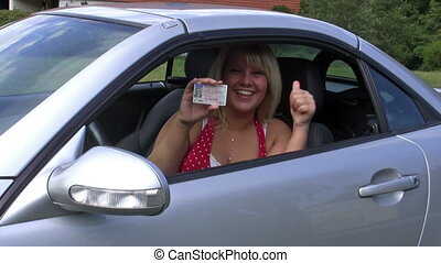 Young woman in her car showing her driver license