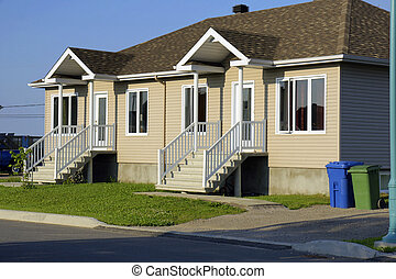 New construction and real estate: beige siding duplex house with recycling and garbage bins.