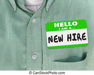 New Hire nametag on a green shirt worn by a new employee or fresh talent just brought onboard to a company or business