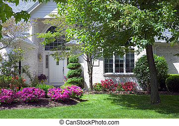 Close-up look at the main entrance to a new home. Beautiful blooming flowers to go with a beautiful new house. Just one of many new home photos in my gallery.