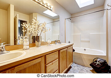 New home bathroom interior with shower and bath combination, wood cabinet
