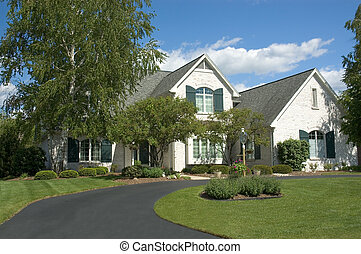 Beautiful white two story brick home. Very colorful photo with blue sky and green grass. Typical new home in the suburbs of the United States. Just one of many home or house photos in my gallery.