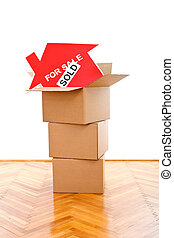 New home concept with house sold sign and cardboard boxes on...