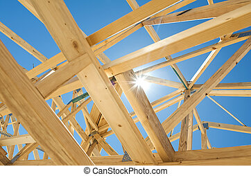 New residential construction home framing against a blue sky and sun