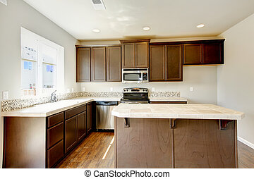 New home kitchen interior with dark brown cabinets.