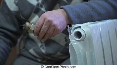 New hot water radiator installation. Closeup of a plumber...