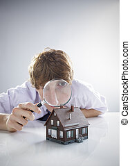 New house concept - Young man holds a magnifying glass over...