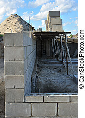 New house construction, building foundation walls using concrete blocks