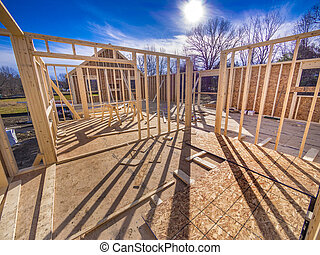 New house framing with studs and flooring being put up