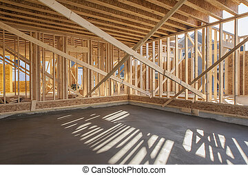 New house interior framing with garage floor just poured