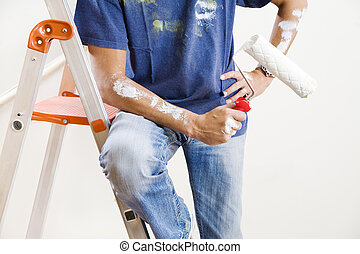 Man holding paint roller in new home, cropped view