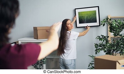New house owners girl and guy choosing place for picture...