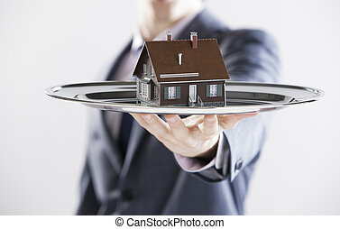 New house - Real estate offer. Businessman holding a silver ...