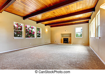 New large empty living room with wood ceiling and fireplace.