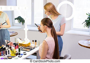 Beautiful young women looking into the mirror