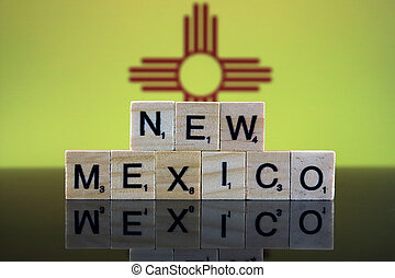 New Mexico State Flag and state name made of small wooden letters. Studio shot.