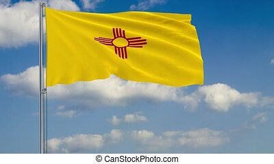 New Mexico State flag in wind against cloudy sky