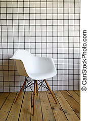 New modern chairs in white standing in white room with white tiles wall