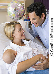 New mother with baby and husband in hospital smiling