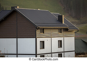 New nice white and brown two-storied cottage with shingle roof in ecological area on foggy wood and hills background on sunny summer day. Well maintained property, real estate concept.