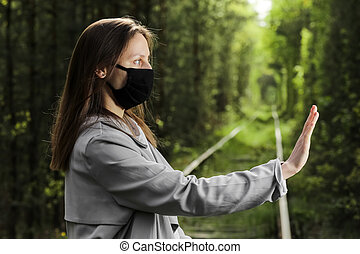 New normal lifestyle of young woman wearing protective mask showing stop coronavirus in the park, enjoy the moment, daydreaming, Concept freedom from covid-19 with medical mask.