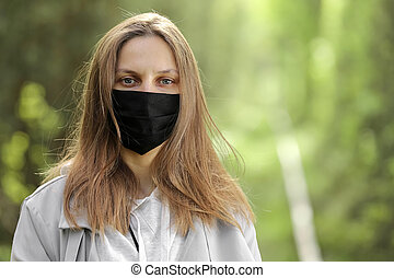 New normal lifestyle of young woman wearing protective mask to relaxing in the park with natural sunlight, enjoy the moment, daydreaming, Concept freedom from covid-19 with medical mask.