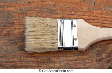 New paint brush on old wooden board construction concept.