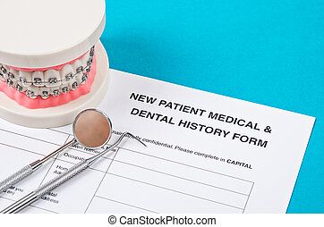 New patient medical form with model tooth and dental instruments.