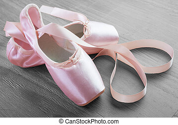 new pink ballet pointe shoes on vintage wooden background