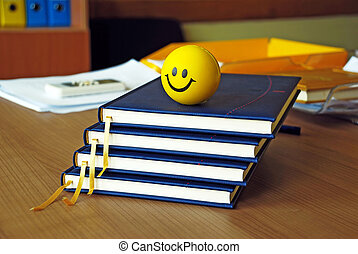 new blue organizers and yellow smiley ball on office desk