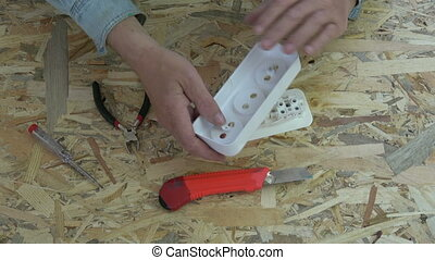 New plastic socket in electrician hands - New white plastic...