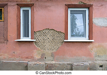 New plastic windows in a crumbling old house wall (contrast)