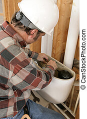 A construction plumber installing a toilet tank in a new building. Authentic and accurate content depiction.