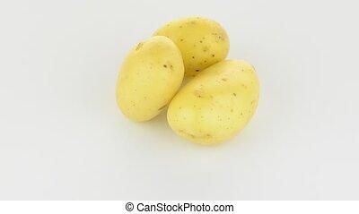 New potato tuber rotating on white background.