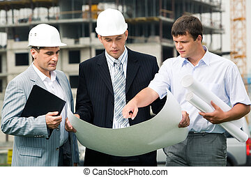 New project - Portrait of three builders standing at...