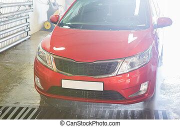 red car at the car wash
