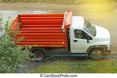 New red dump truck with white cab is empty, ready for transportation