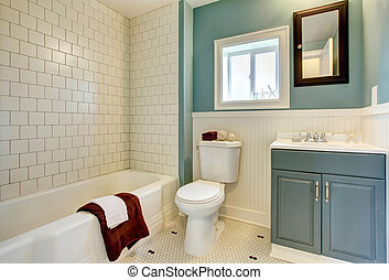 New remodeled blue bathroom with classic white tile. -...