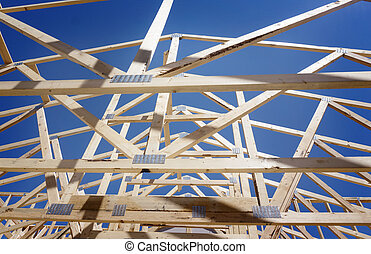 New residential construction home framing against a blue sky...