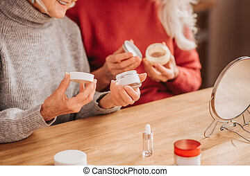 Two good-looking elderly women holding new creams