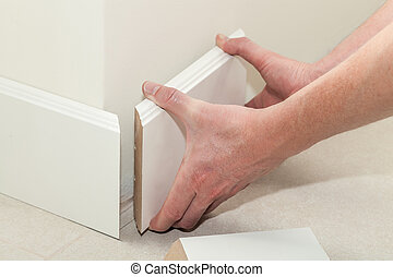 New skirting board - Man putting new skirting board in house